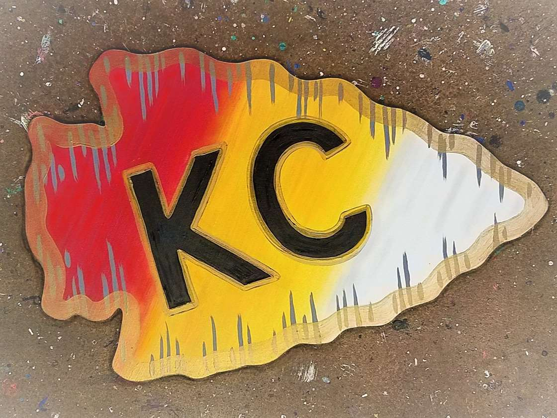 Showing Our Pride is painted on a wood sign